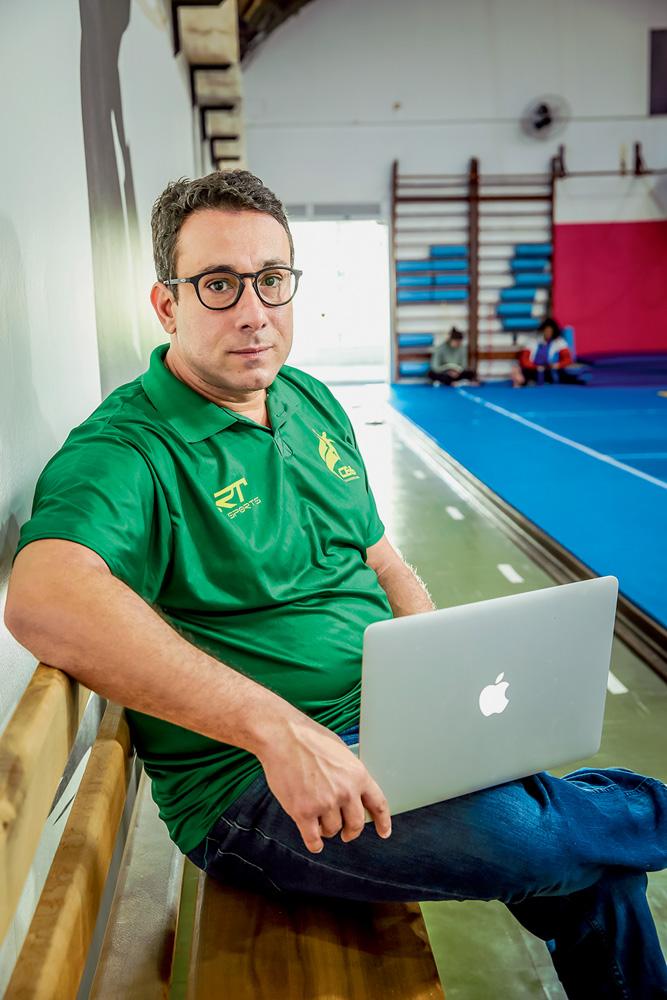 A imagem mostra Tatá, com um notebook no seu colo, sentado em um banco de madeira à beira de uma quadra. Ele está com expressão serena e o uniforme da comissão técnica brasileira.