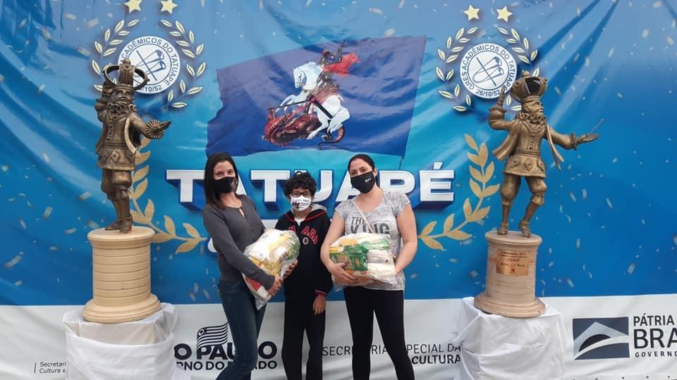 A imagem mostra três pessoas segurando sacos de arroz, todas de máscara. Ao fundo há um bandeirão com escudos e o nome da Acadêmicos da Tatuapé