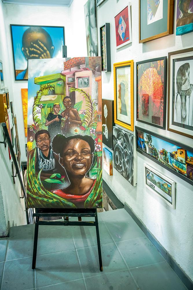 Quadro em cavalete. Pintura mostra uma menina e três meninos negros sorrindo. Folhas rodeiam eles e há casinhas atrás