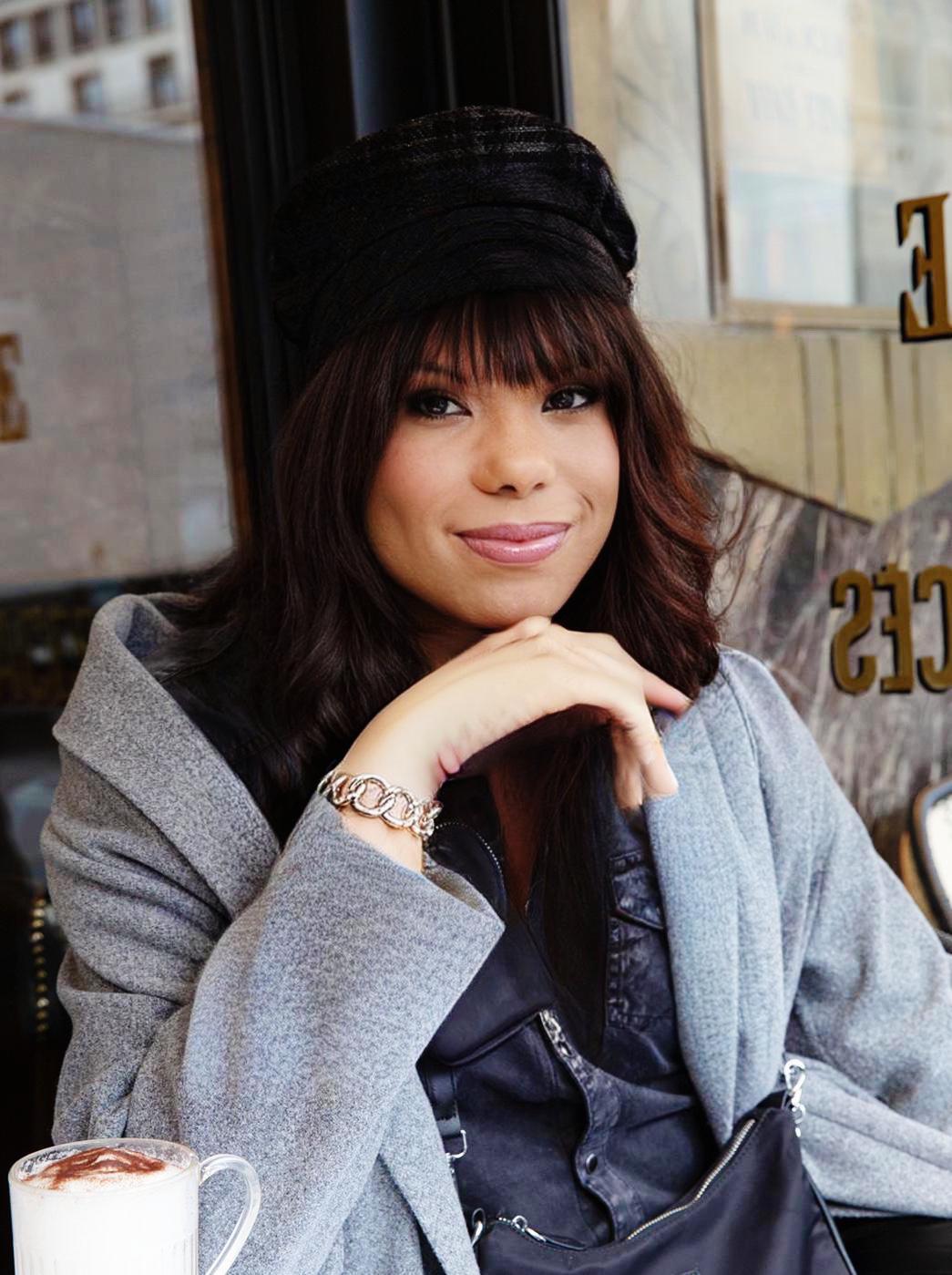 Valentina Saluz sorri para a câmera. Veste blusa cinza e chapéu preto.