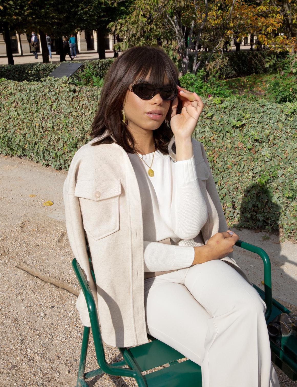 Valentina Saluz posa sentada em praça com óculos escuros e roupas brancas.