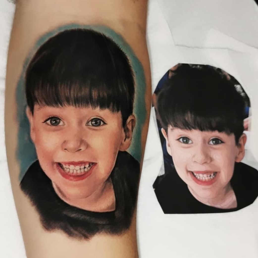 Um braço com uma tatuagem de uma criança sorrindo, ao lado uma foto recortada desta tatuagem