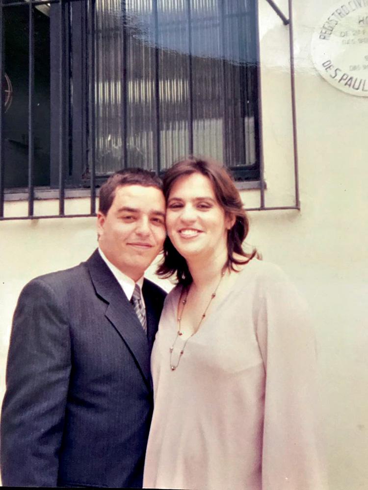 luciano e adriana sorriem para a foto, com roupas sociais, na ocasião do seu casamento no civil