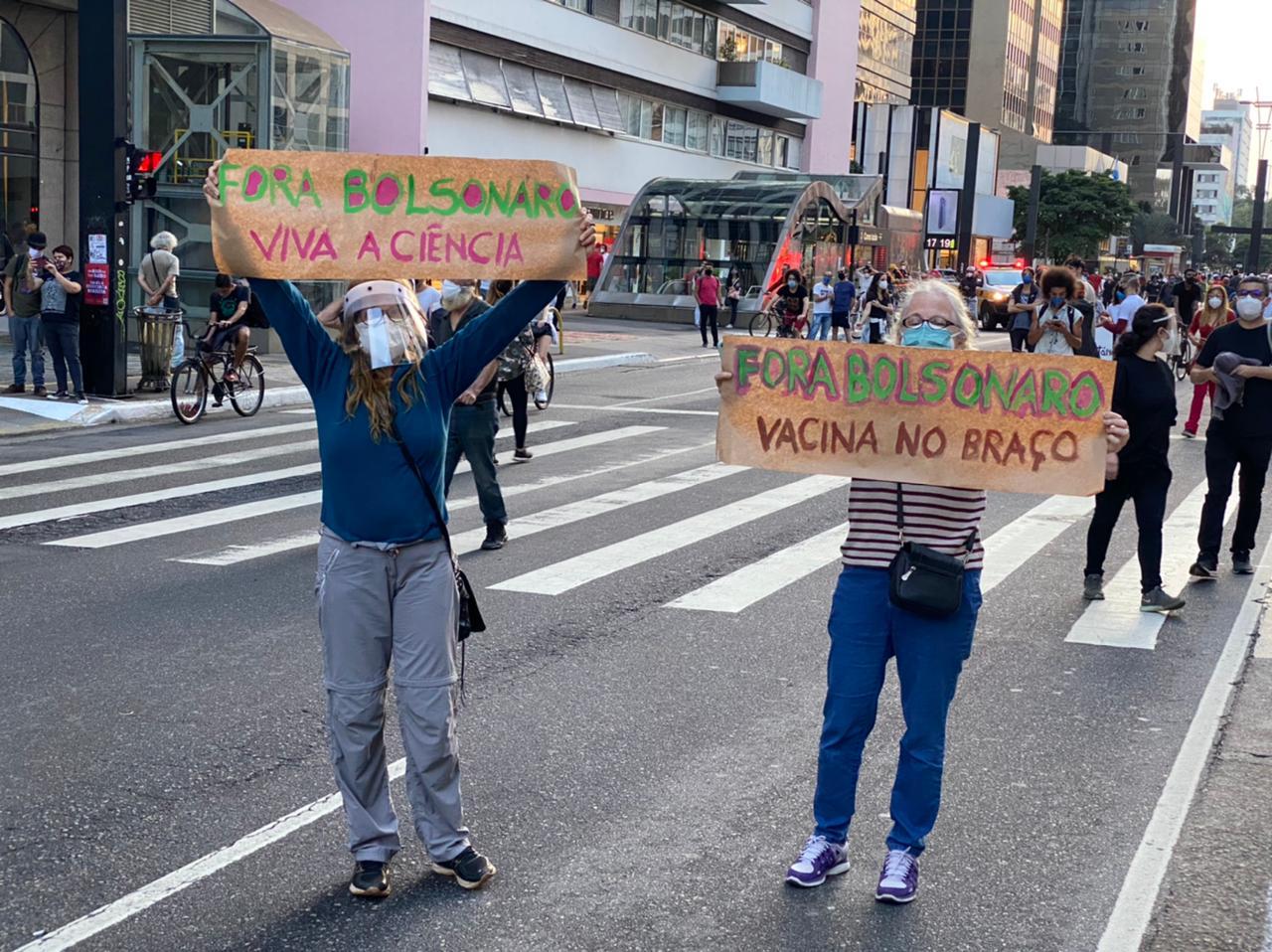 Imagem mostra duas mulheres com máscara segurando cartazes que dizem: