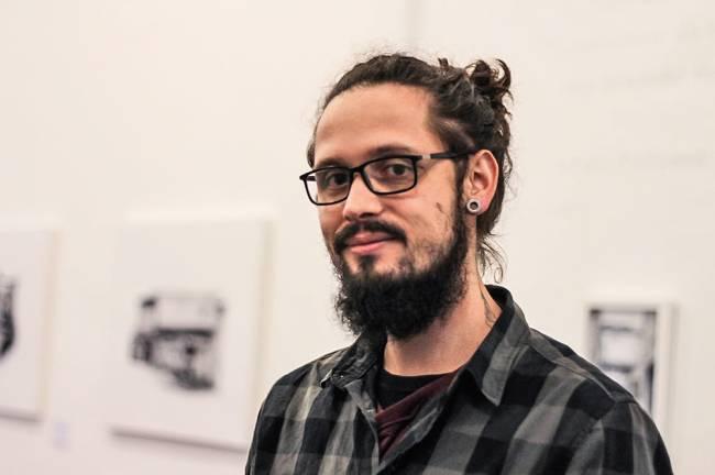 Homem de óculos e cabelo em um coque posa para foto