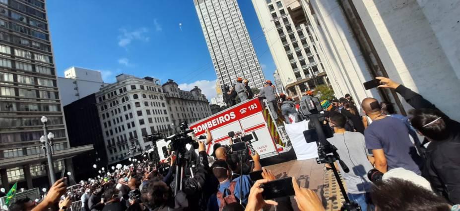 Imprensa ao lado de carro de bombeiros que leva caixão de Bruno Covas