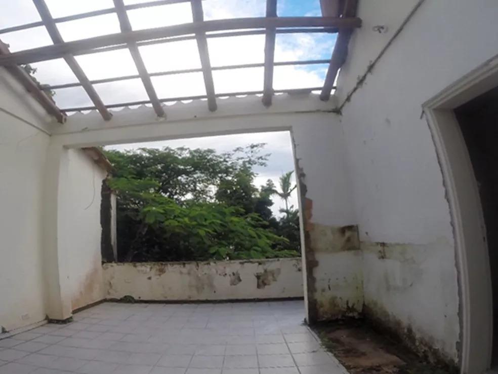 Interior de uma casa, com vão aberto para árvores, tem mofo nas paredes