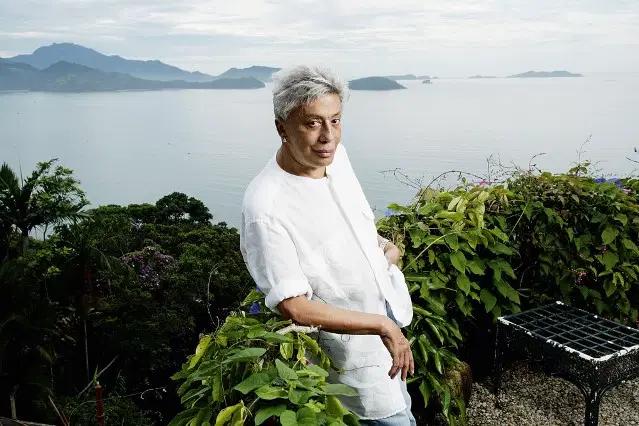 Homem posa de branco em cima de uma casa que tem vista para o oceano