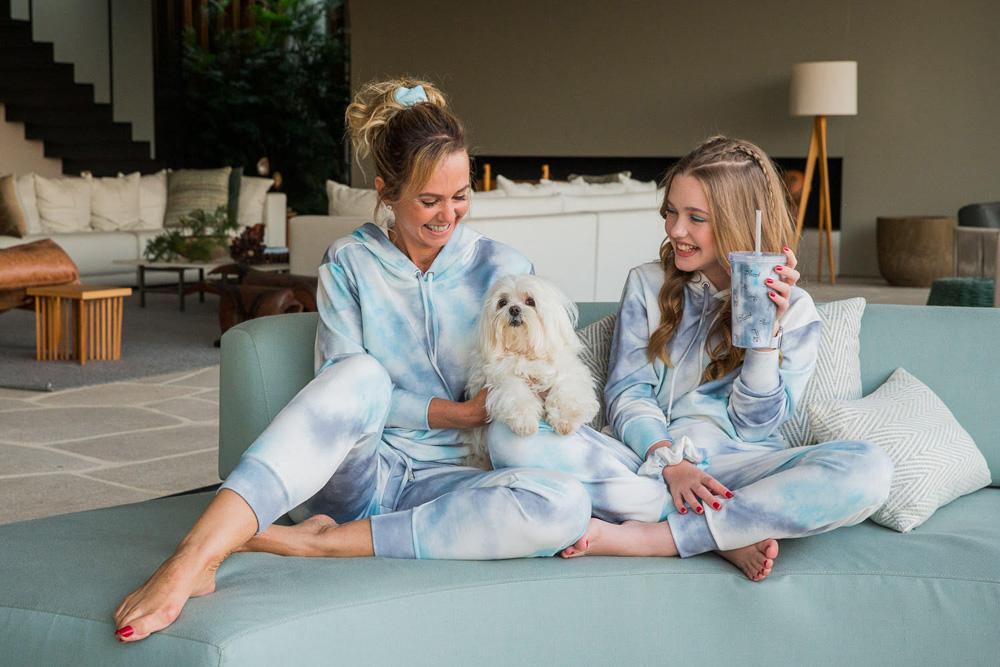 A imagem mostra Deborah, sua cadela e sua filha todos em cima de um sofá, se divertindo. As duas estão usando as mesmas roupas azul claro.