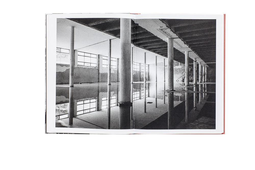Imagem em preto e branco mostra um armazém vazio, com água e reflexos no chão