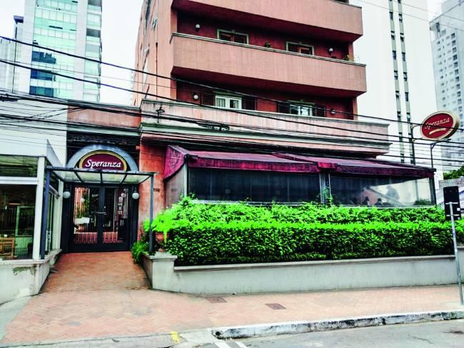 Fachada de prédio com jardim avarandado na frente e pizzaria Speranza no térreo.