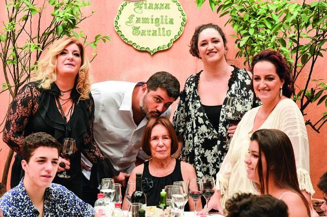 Família envolta de mesa de almoço com senhora matriarca ao centro e homem abaixado beijando o topo de sua cabeça.