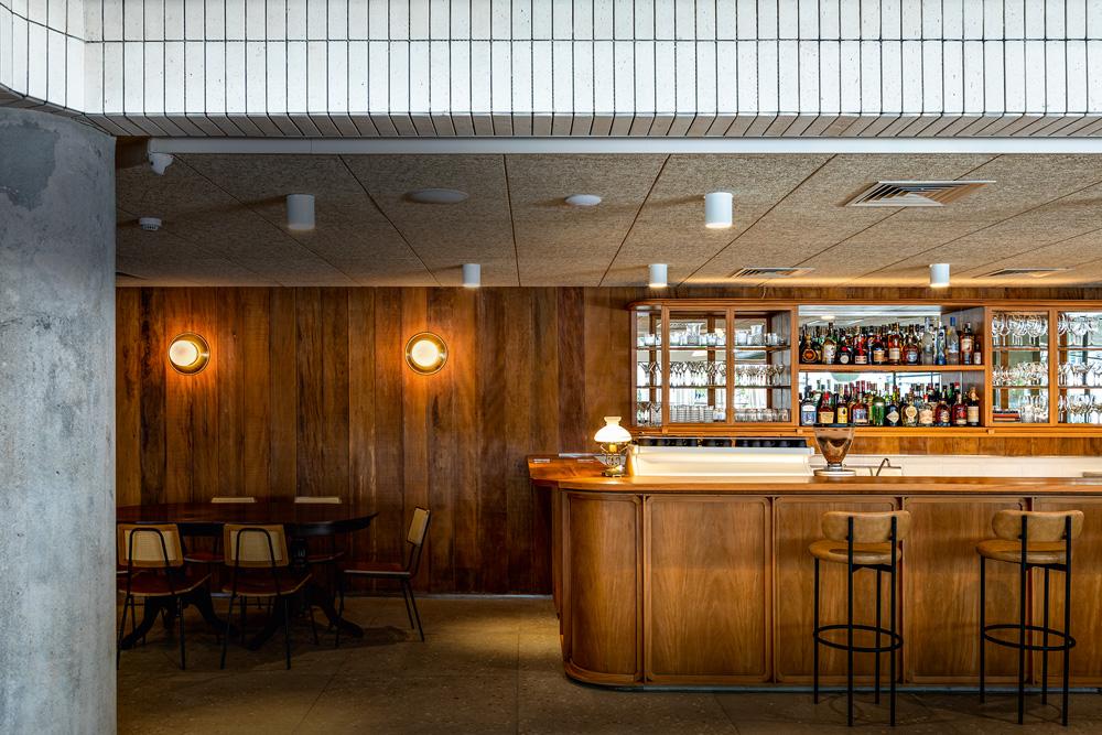 Ambiente do bar do restaurante Fattoria Ráscal, com parede ao fundo, balcão e banquetas na porção direita e mesa com cadeiras, à esquerda, de madeira.