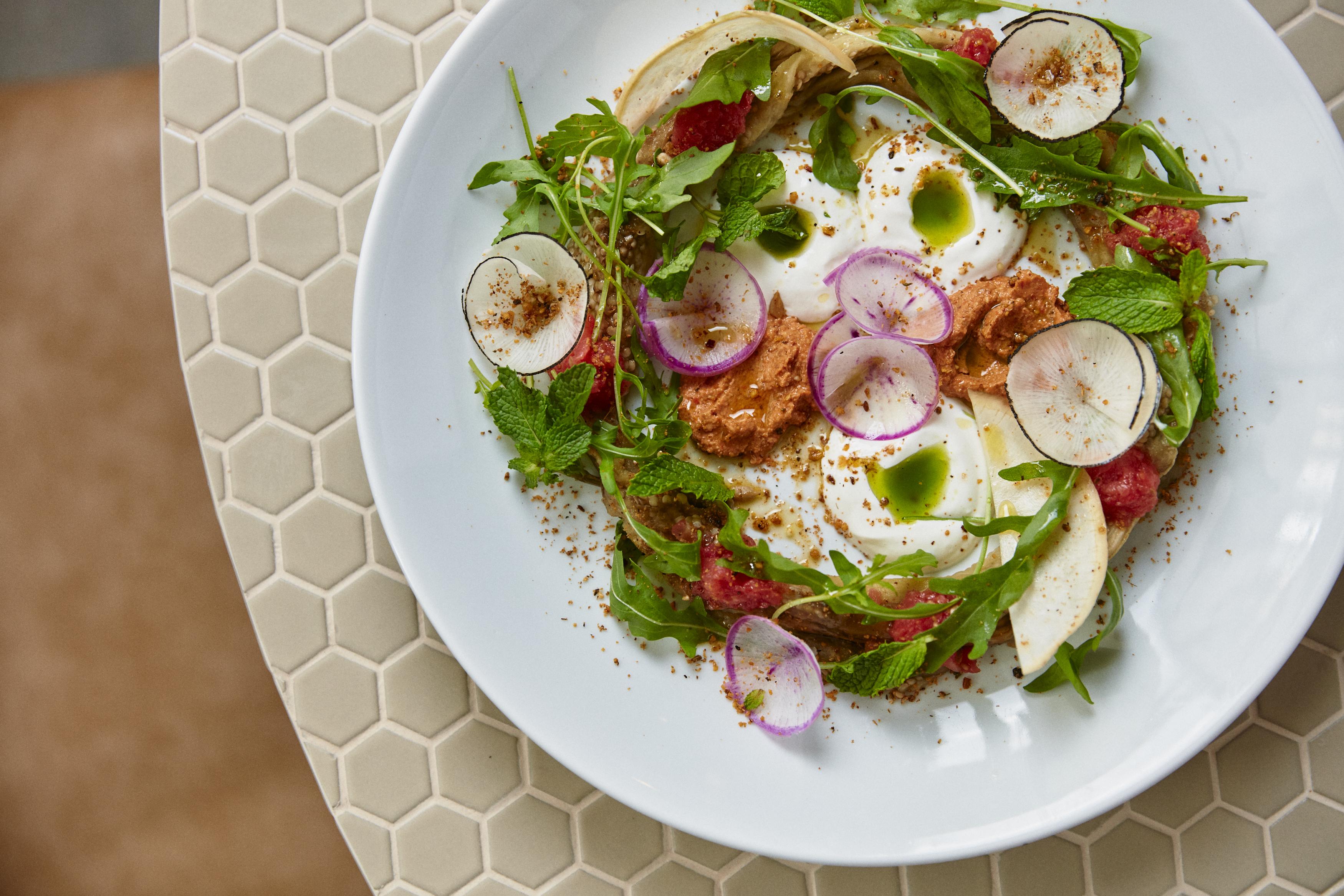 Prato de porcelana branco sobre ladrilhos hexagonais. Salada com folhas de hortelã, rabanetes em formatos de flores, coalhada, folhas de minirrúcula, pasta de pimentão vermelho e nozes coberta por sementes.