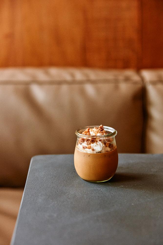 Ponta de mesa de pedra cinza com pote de vidro com flã de caramelo coberto por chantili, pedaços de avelã e nozes.