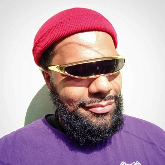 Homem negro com barba e touca vermelha usa um óculos metálico sem separação para cada olho
