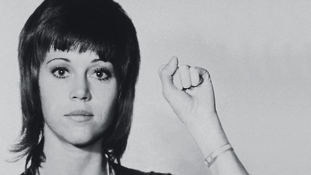 A imagem é um retrato de Jane Fonda em que ela está com o punho esquerdo erguido