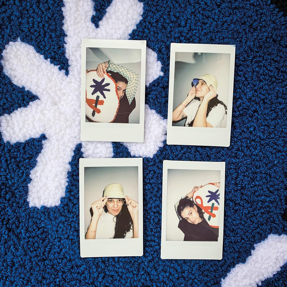 Quatro fotos em polaroid, de meninas segurando peças de tapeçaria azul, são postas na mesma peça de tapeçaria
