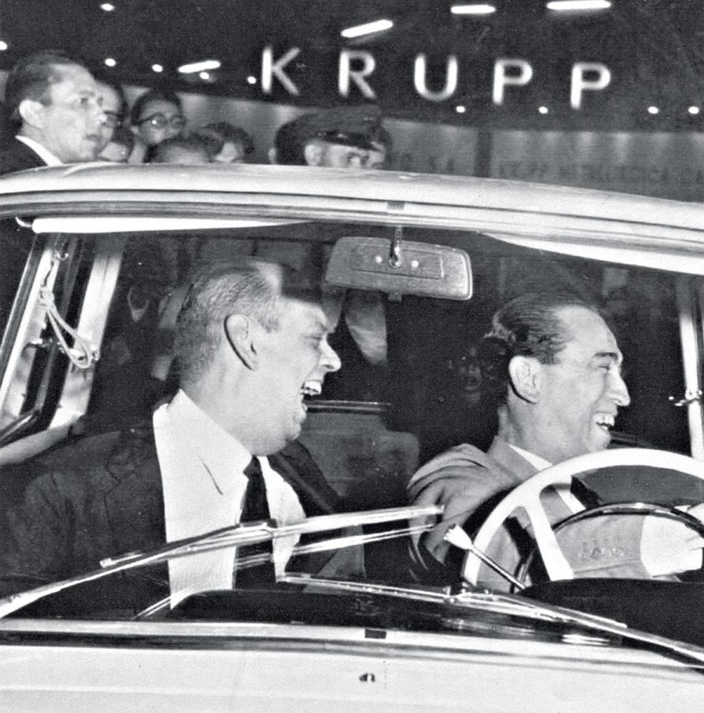 A imagem mostra Caio de Alcântara Machado e Juscelino Kubitschek dentro de um carro, com Juscelino no volante e os dois rindo ao olhar à direita.