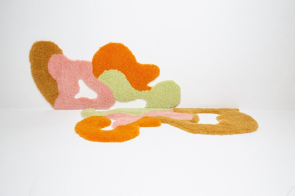 Uma peça de tapeçaria abstrata com formas arredondadas em laranja, marrom, rosa e verde