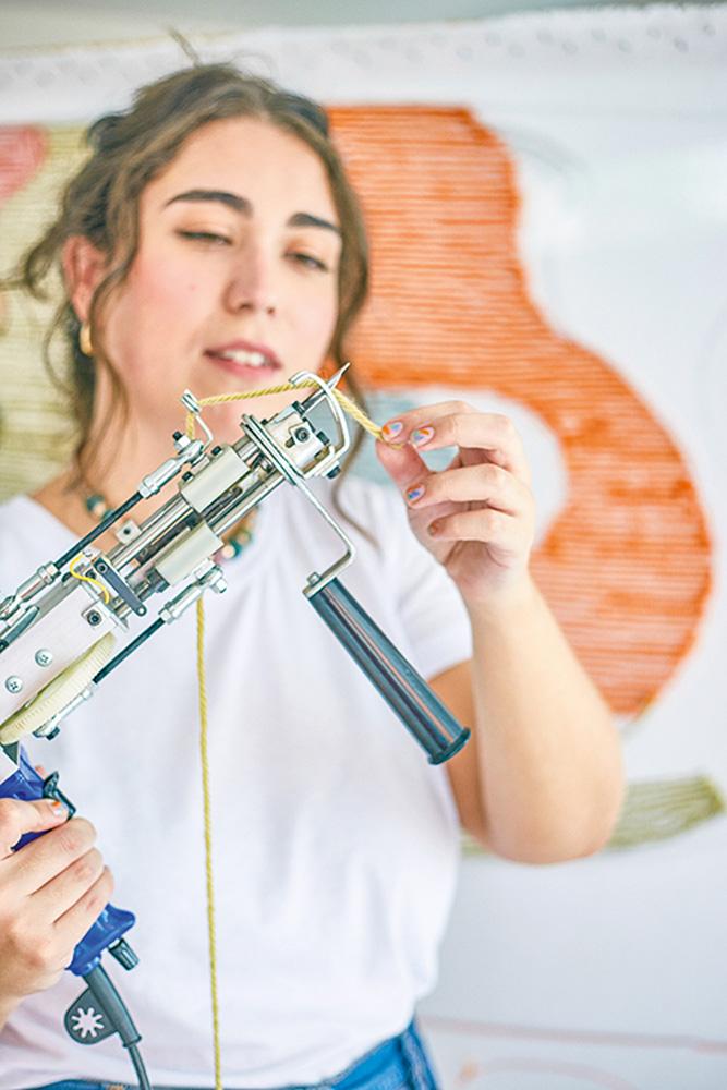 Mulher segura e olha para uma pistola de tufting (tapeçaria)