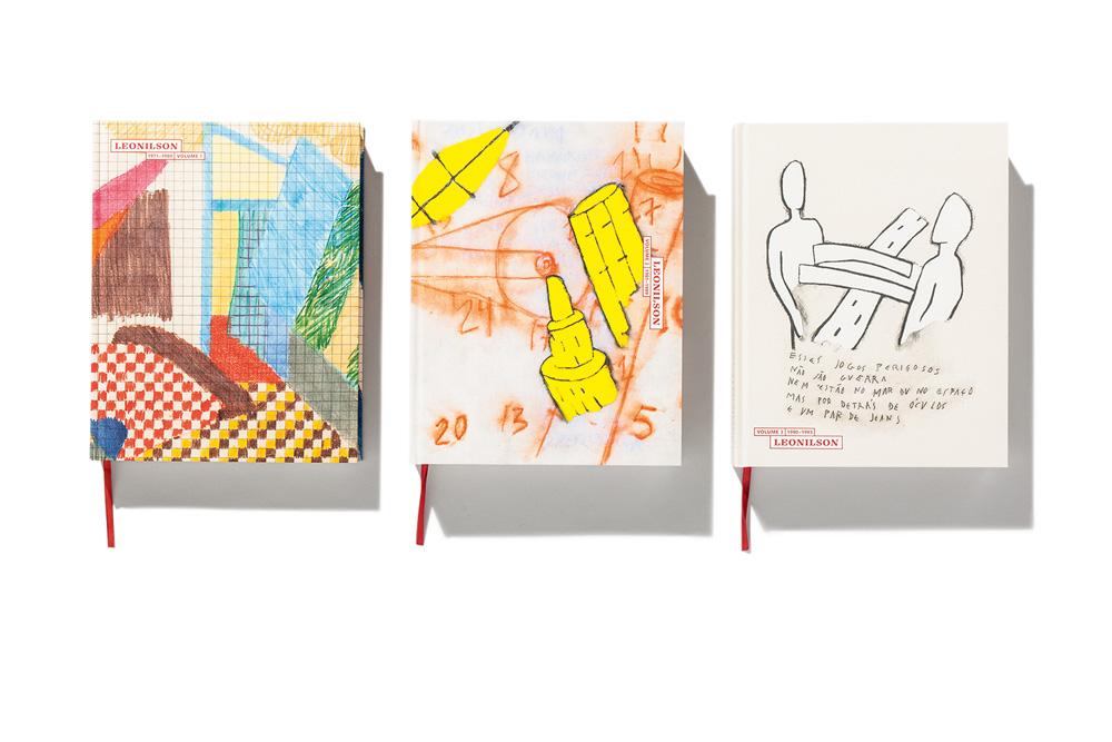 3 livros um ao lado do outro. Um tem capa abstrata e colorida, outra é amarela e laranja, com números e formas abstratas e a terceira tem desenho de um corpo entrelaçado com uma estrada