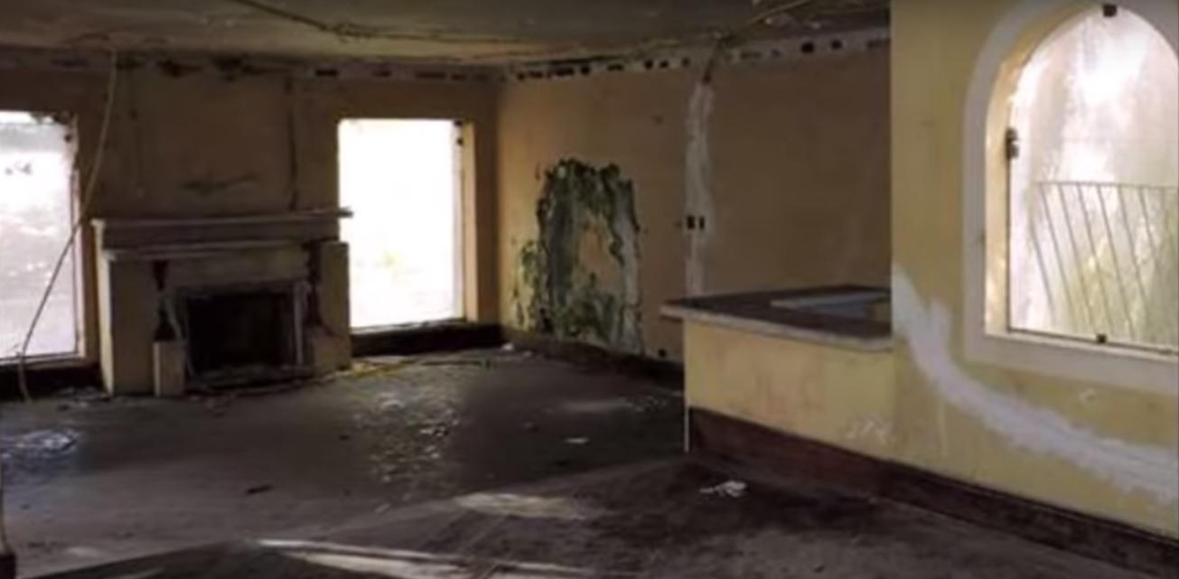 Interior de um imóvel vazio, sem pintar, com mofos e rachaduras nas paredes