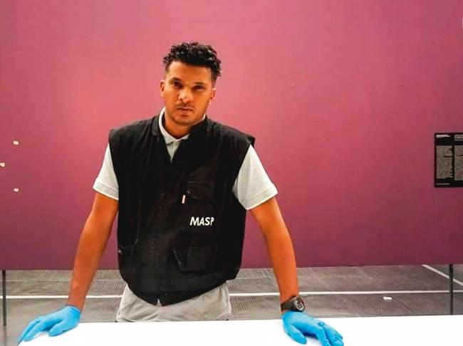 Homem com colete preto e luvas azuis apoia sua mão em uma bancada branca. Está na frente de uma parede rosa