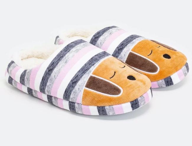 Um par de pantufas de pelúcia tem estampado listras roxo e rosa e um cachorro em laranja