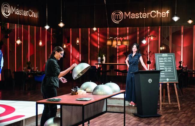 No estúdio do MasterChef. Paola vestida de preto à esquerda. Ao fundo a apresentadora Ana Paula Padrão vestida de preto, encostada em púlpito do programa.