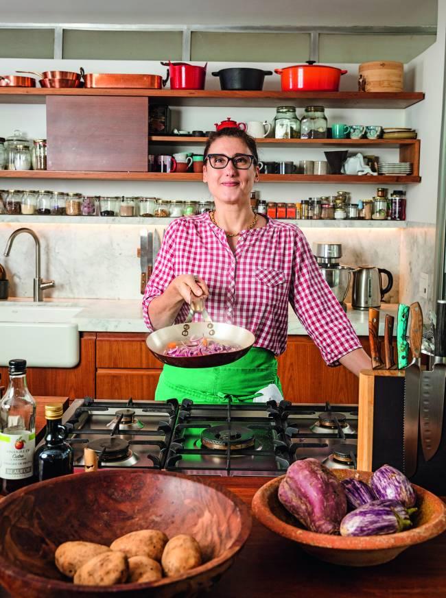 Paola Carosella vestida com camisa xadrez vermelho e branco segurando frigideira dentro de sua cozinha.