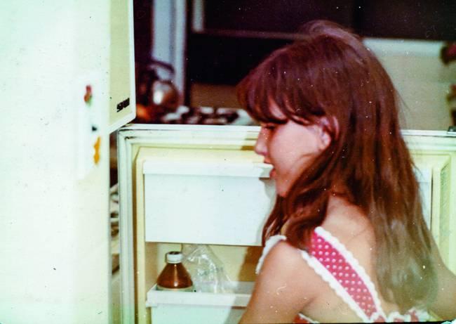 Menina (Paola) abrindo porta da geladeira.