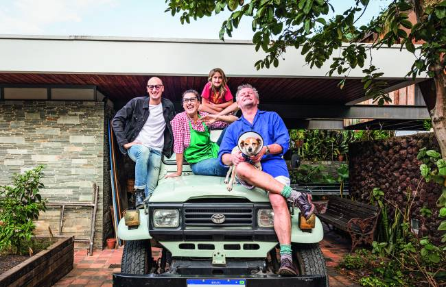 Família sobre jipe em frente à casa. Homem à esquerda, Paola Carosella ao centro, criança no topo e homem grisalho com cachorro no colo (à direita).