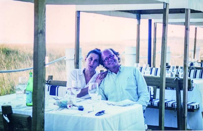 Mulher (à esquerda) e homem sentados abraçados em mesa de restaurante.