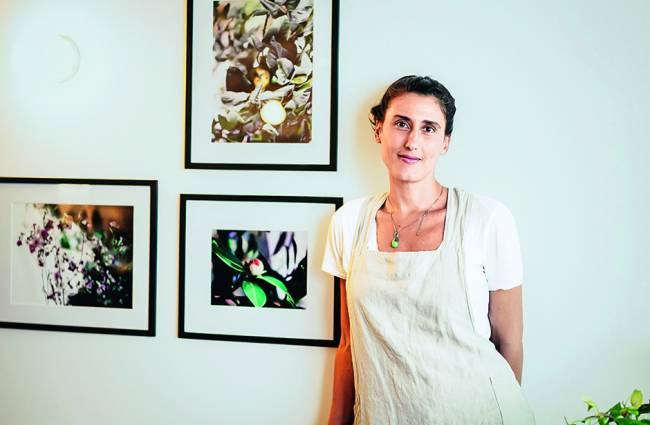 Paola Carosella encostada em parede branca com três quadros.