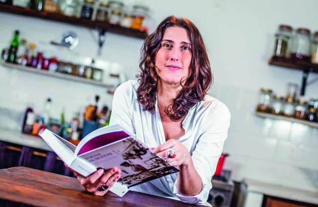 Paola Carosella (mulher branca de cabelo castanho) sentada atrás de bancada de madeira folheando livro.