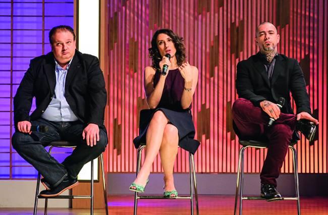 Três jurados do MasterChef sentados em banquetas em cima de palco de madeira. À esquerda, Erick Jacquin, Paola Carosella ao centro e Henrique Fogaça à direita.