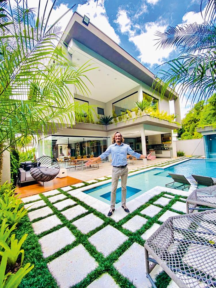 A imagem mostra Caio bem, pequeno, em frente à uma mansão enorme, de dois andares, árvores em volta e piscina.