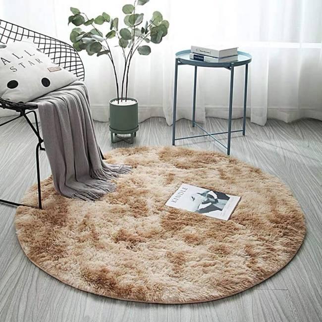 Um tapete bege de pelúcia está em uma sala. Há também um vaso, uma mesa de canto e uma poltrona na foto
