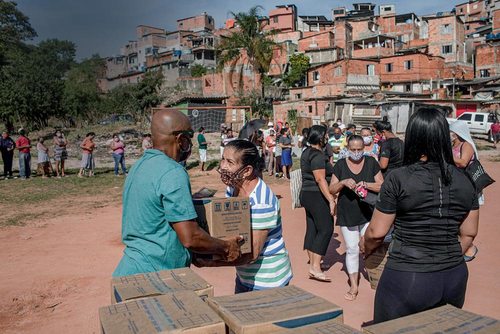 A imagem mostra uma fila de pessoas de máscara recebendo caixas de papelão. Ao fundo, há uma favela.