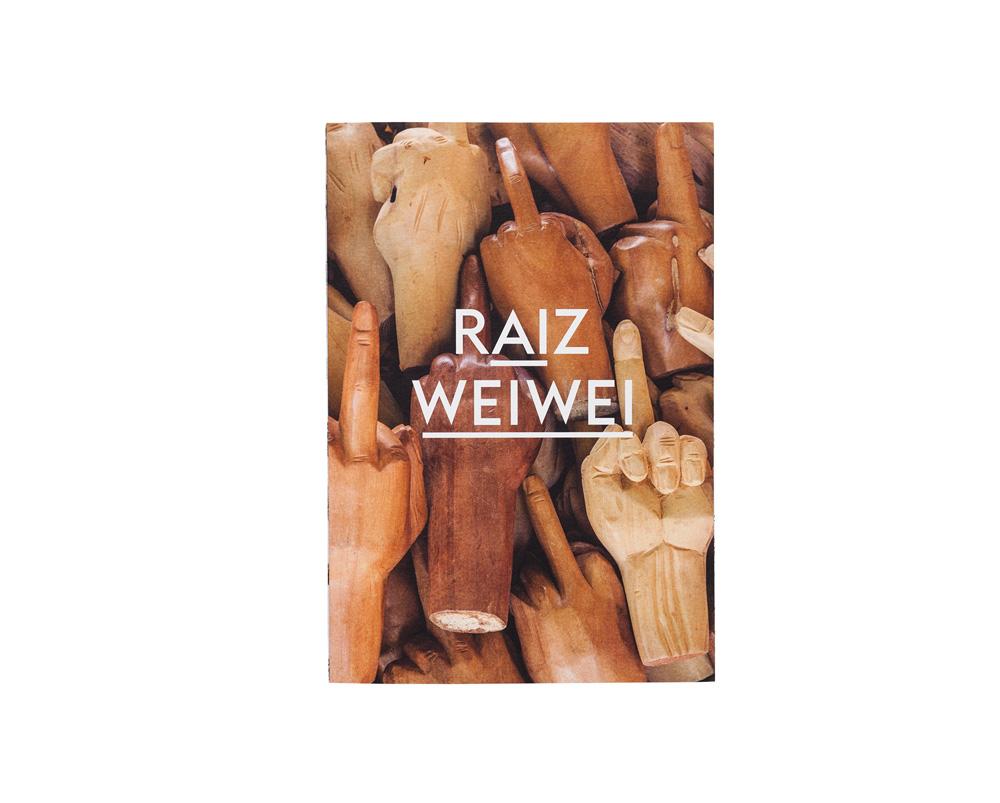 Catálogo da mostra do artista chinês Ai Weiwei. Tem várias mãos em madeira mostrando o dedo do meio