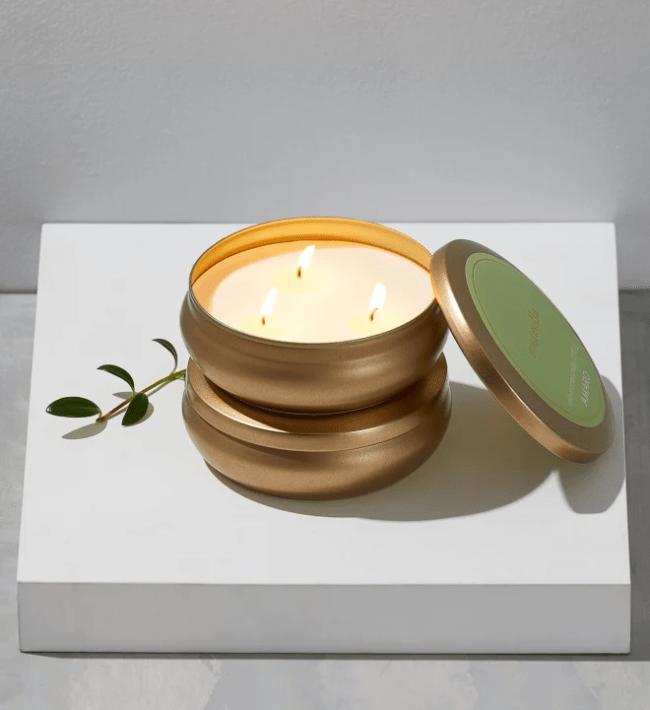 Em uma caixa branca, uma vela com três pavios acesos em estrutura dourada. A tampa está apoiada ao lado e é verde