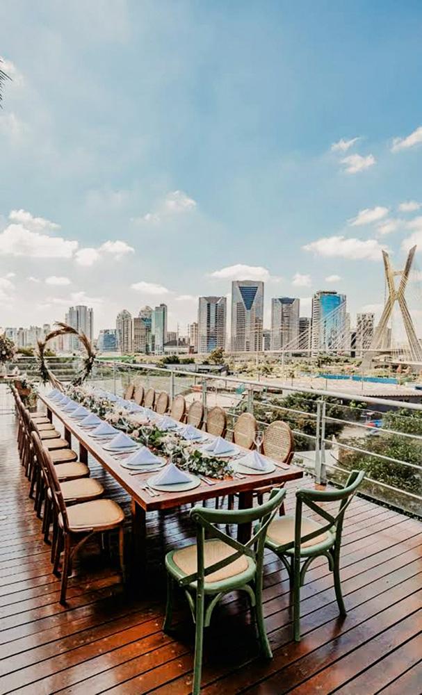 Foto mostra uma mesa formal, com muitos lugares, a céu aberto. Ao fundo, a cidade de São Paulo e prédios espelhados. Céu azul