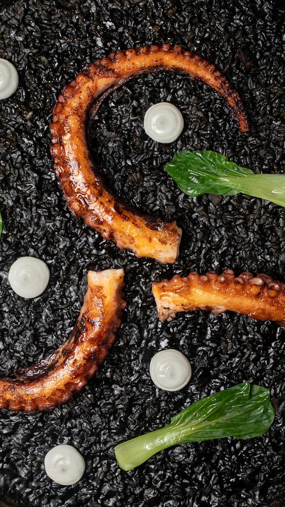 Foto aérea de arroz negro com tinta de lula e tentáculos de polvo grelhado espalhados por cima junto de bolinhas de aïoli.