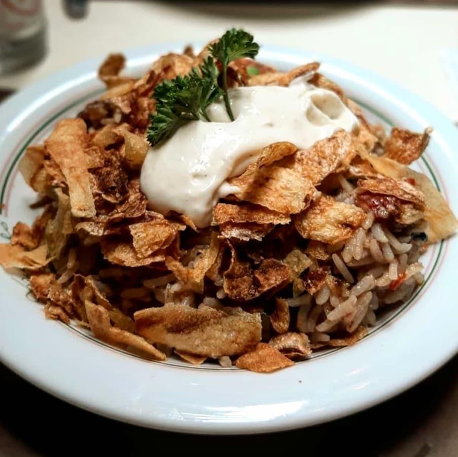 Prato funco com arroz com carne de panela do Muquifo coberto por casquinhas de batata frita e aïoli.