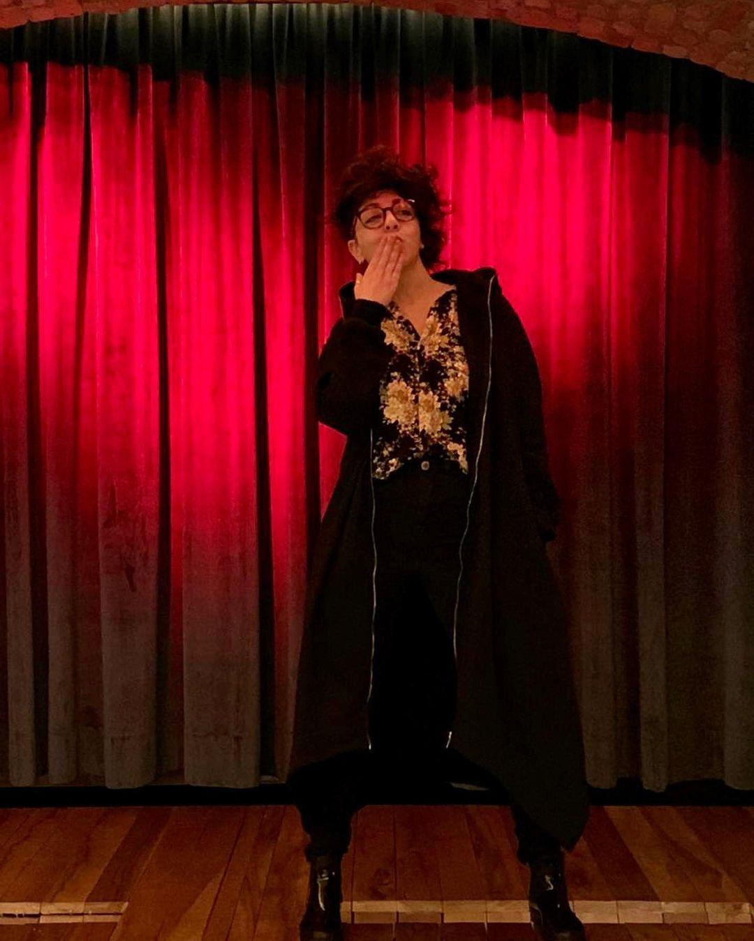 Mulher sobre um palco com uma cortina vermelha atrás