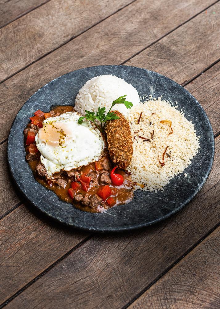 Prato de pedra sobre mesa de madeira com arroz, feijão, picadinho, ovo frito, bolinho alongado e farofa.