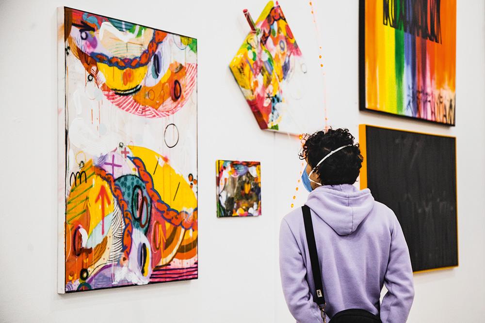 Uma mulher observa uma mostra. Há quadros na parede. O que ela olha é colorido e abstrato