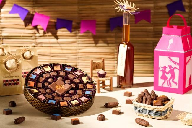 Caixa redonda de chocolate da Chocolat du Jour temático de festa junina ao lado de cestinha de cestinha com milhos de chocolate em cenário com banderolas rosas e roxas.