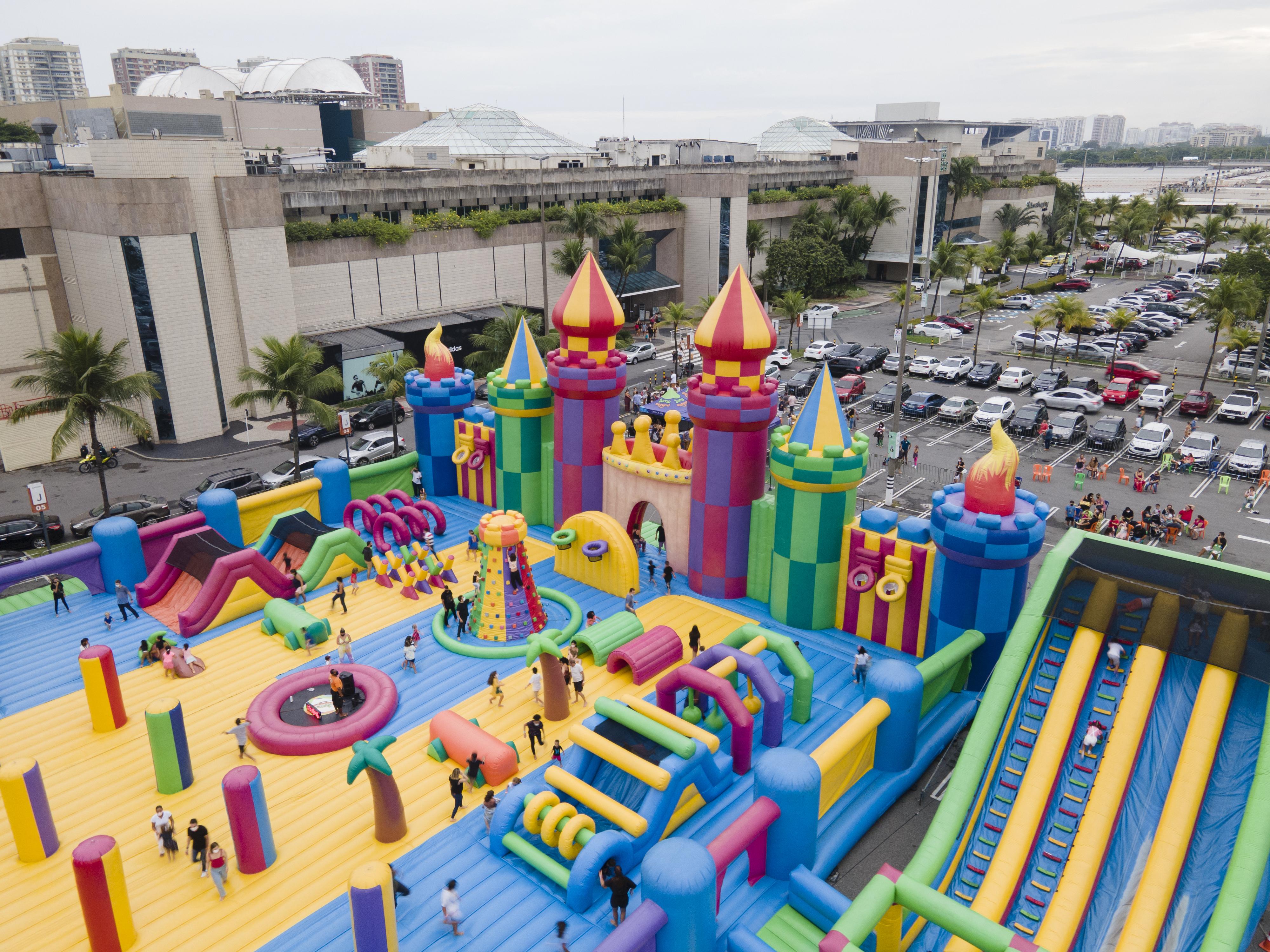 No estacionamento de um shopping, crianças brincam em uma estrutura inflável em formato de castelo colorida. Há carros em volta